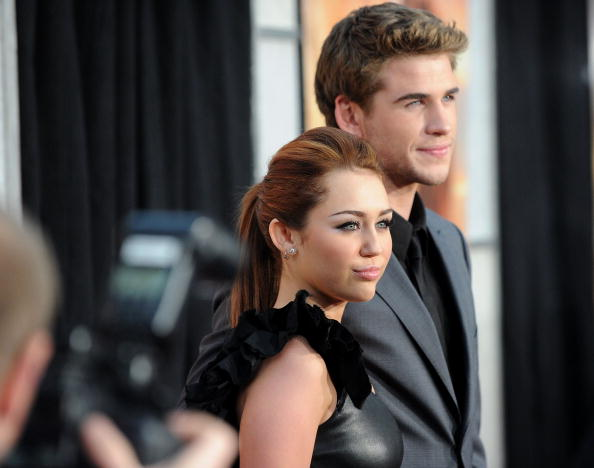 """LOS ANGELES, CA - MARCH 25:  Actress/singer Miley Cyrus (L) and actor Liam Hemsworth arrive at the premiere of Touchstone Picture's """"The Last Song"""" held at ArcLight Hollywood on March 25, 2010 in Los Angeles, California.  (Photo by Jason Merritt/Getty Images)"""
